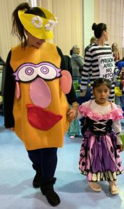 Teacher dressed as Mrs. Potato-Head arrives with preschooler dressed as a princess.
