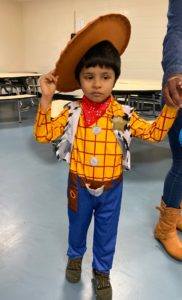 A preschooler dressed as a cowboy arrives